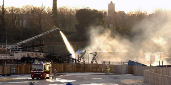 The scale of the devastation is clear as firefighters dampen down the site