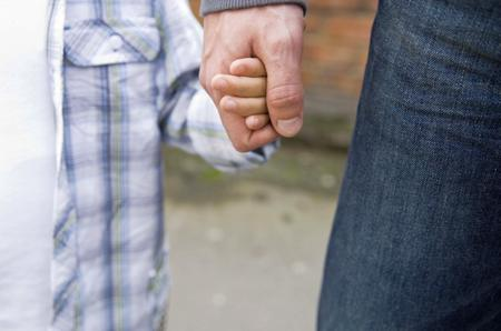 Child holding hands with an adult