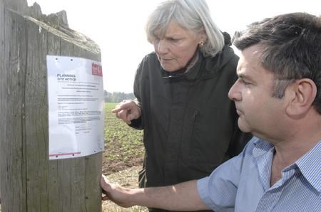 Julia Pender and David Luck inspect the planning notice for the proposed compost plant site in Venson Road, Tilmanstone.