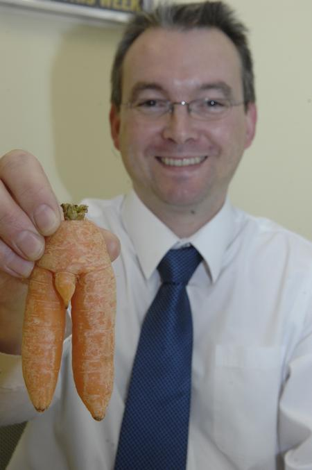 Mark Eastham with the suggestively-shaped carrot bought from Sainsbury's in Ashford