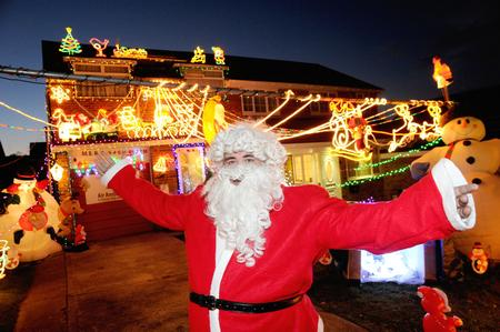 Andy Broad dressed as Father Christmas to switch on the lights outside his house in Cliffe Woods