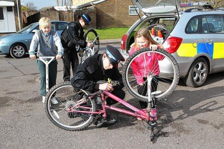 PCSO Ian Henderson marks Courtney Evan's bicycle with an invisible security permanent marker
