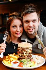 KMFM breakfast presenters take on the challenge. Rob and Emma with the giant burger