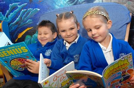 Nojus, six, Kacey and Mia, both five, from Milton Court School delve into a selection of books at Sittingbourne Library