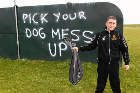 Leysdown FC groundsman John Osmond with a bag of dog poo picked up from the pitch