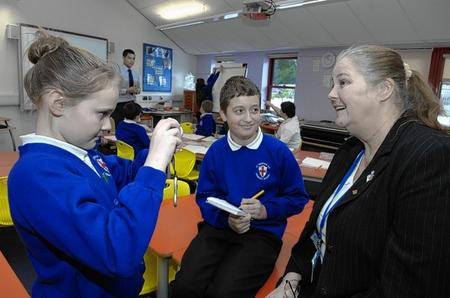 Mary Cox,11 and Louie Arthur, 10, photograph and interview teacher Miss Tracey Parker during a lesson about journalism