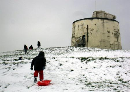 Sledgers tredge up a hill to a Martello tower in Folkestone
