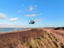Kent Air Ambulance coming in to land on the sea wall along the Saxon Shore Way close to Upchurch