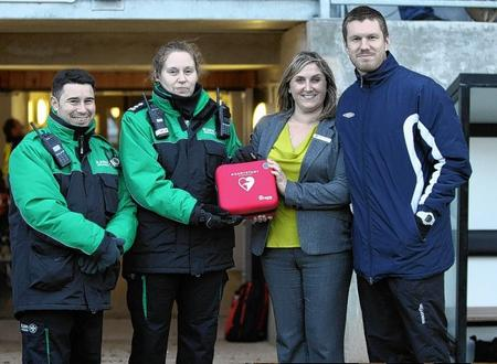 St John Ambulance volunteers Philip Winchester and Jo Eade presenting the defibrillator to DFC representatives Clare Weeks and First Team Captain, Elliot Bradbrook
