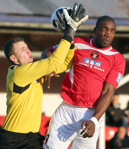 Dartford goalkeeper Marcus Bettinelli collects as Elder challenges