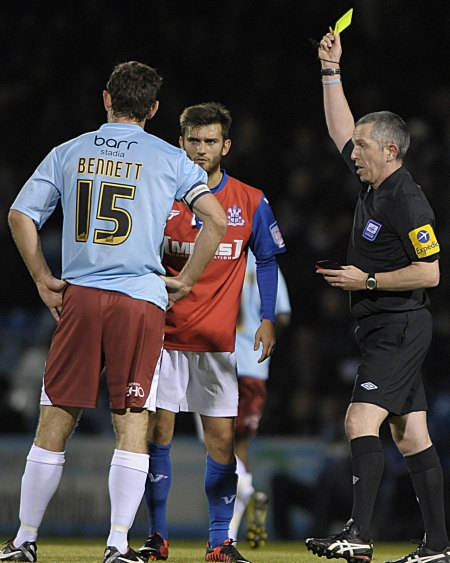 Jack Payne is booked while Cheltenham captain Alan Bennett watches on