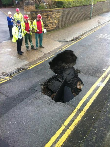 Workmen fix a hole in Hill's Terrace, Chatham, caused by a burst water main.