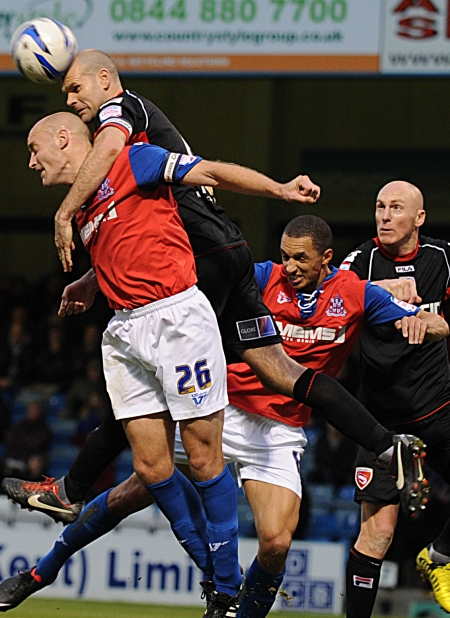 Adam Barrett is outjumped in this aerial battle