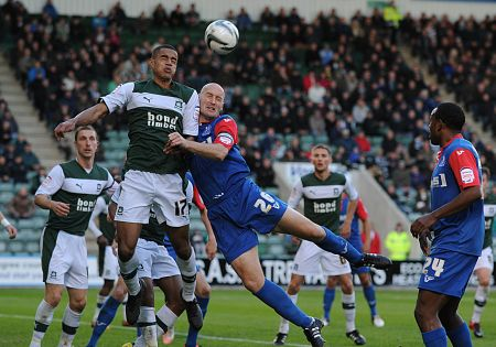Adam Barrett goes in for a header with Plymouth defender Curtis Nelson