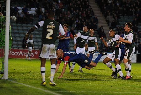 Gillingham captain Adam Barrett heads in a late equaliser against Plymouth