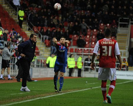 Charlie Lee pushes Gills forward with a throw as boss Martin Allen looks on