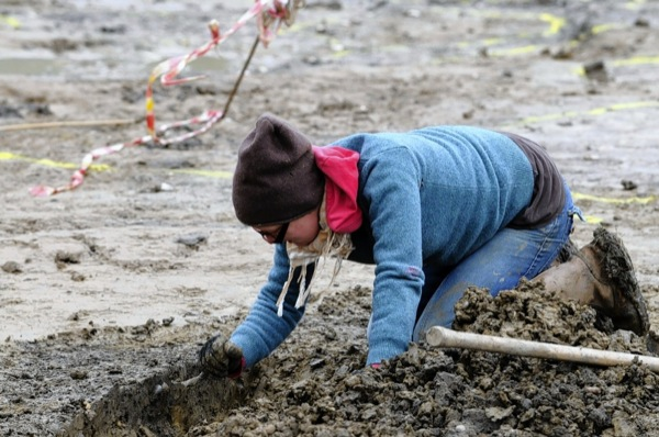 Nina Olofsson down on hands and knees as she scrapes through the soil.