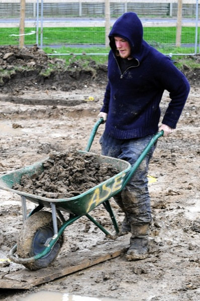 Tom Profitt moves a barrow of very heavy topsoil off the dig.